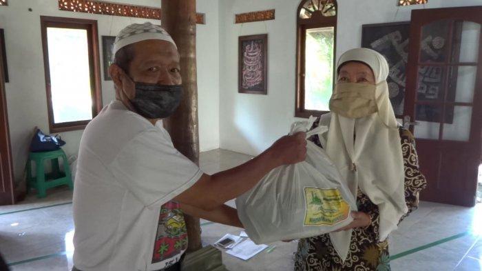 Warga menerima bantuan sembako dari Masjid Al Amien