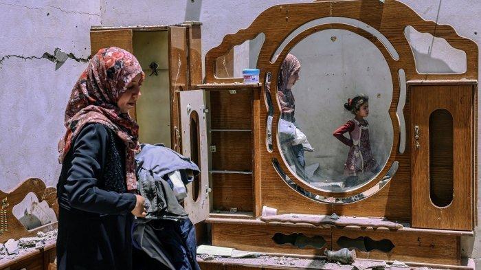 Seorang wanita warga Palestina mencari harta benda keluarga di rumahnya, setelah dihancurkan oleh serangan udara Israel, di kota Rafah, di Jalur Gaza selatan pada 16 Mei 2021.