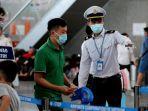 anggota-staf-pusat-pengendalian-penyakit-vietnam-membantu-para-penumpang-di-bandara-da-nang.jpg