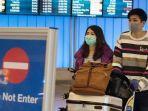 para-pelancong-yang-tiba-di-bandara-internasional-los-angeles-mengenakan-topeng-pelindung.jpg
