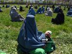 wanita-mengenakan-burqa-menggendong-anak-saat-menunggu-gandum-gratis-dari-pemerintah-afghanistan.jpg
