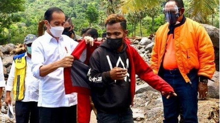 Jokowi melepas jaket merah yang dipakai lalu memberikannya kepada pemuda yang merupakan pengungsi korban bencana di NTT.