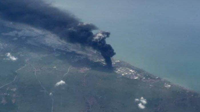 KEBAKARAN KILANG BALONGAN- Asap hitam membumbung di atas area kilang minyak Pertamina Balongan, Indramayu, Jawa Barat, terlihat dari kabin penumpang pesawat Batik Air ketika melintas di pesisir utara Pulau Jawa dalam penerbangan dari Bandara Soekarno-Hatta Tangerang menuju Bandara Adisoemarmo, Solo, Senin (29/3/2021), sekira pukul 12.34 WIB. Kebakaran di Kilang Pertamina Balongan terjadi pada tangki T-301G, Senin 29 Maret 2021 mulai sekitar pukul 00.45 dini hari. (TRIBUNNEWS/VOVO SUSATIO)
