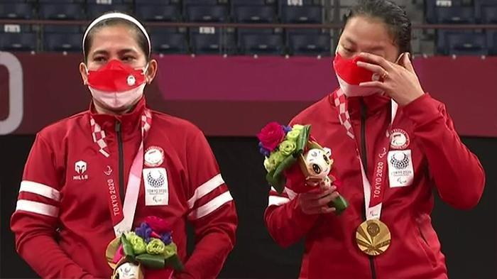 Pasangan ganda putri Paralimpiade Tokyo dari Indonesia, Khalimatus Sadiyah (kanan) Leani Ratri Oktila (kiri) meraih medali emas, Sabtu (4/9/2021). Tampak Khalimatus Sadiyah menghapus air matanya usai lagu Indonesia Raya berkumandang.