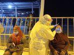 pekerja-migran-indonesia-saat-dilakukan-swab-oleh-petugas-kesehatan-di-kabupaten-nunukan.jpg