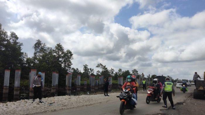 Polisi mengatur lalu lintas di kawasan Bukit Rawi Pulang Pisau Kalimantan Tengah yang jalannya mengalami kerusakan setelah dilanda banjir selama berhari-hari akibat luapan Sungai Kahayan