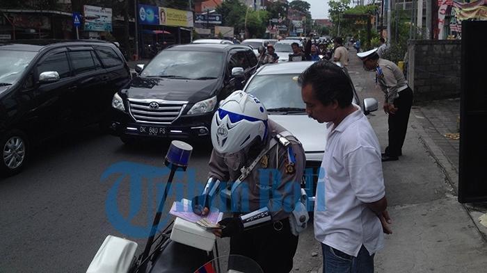 Seorang pengendara mobil mendapat peringatan dari polisi karena parkir di pinggir jalan Teuku Umar, Kamis (3/3/2016)