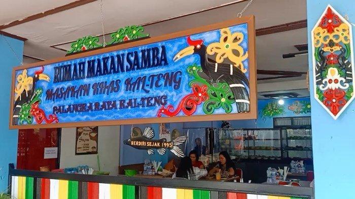 Papan nama Rumah Makan Samba bermotifkan ornamen dan ukiran khas Dayak Kalimantan Tengah berada di atas bangunan.