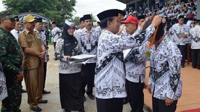 Wakil Bupati Kapuas HM Nafiah Ibnor menyerahkan penghargaan kepada guru berdedikasi dan berprestasi di momen upacara peringatan HGN dan HUT ke 73 PGRI tingkat Kabupaten Kapuas