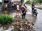 warga-dan-polisi-bergotong-royong-membersihkan-selokan-yang-tersumbat-untuk-mencegah-banjir.jpg