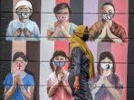 warga-melintas-di-dekat-mural-bergambar-simbol-orang-berdoa-menggunakan-masker.jpg