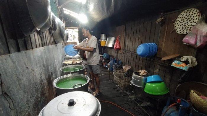 Anak dari Maskota Muradiah saat berada di dapur olahan miliknya, sedang menuang olahan kue talam ke sebuah panci. Proses memasak ini dibutuhkan waktu satu-setengah jam hingga dua jam lamanya. TRIBUNKALTIM.CO/MOHAMMAD FAIROUSSANIY