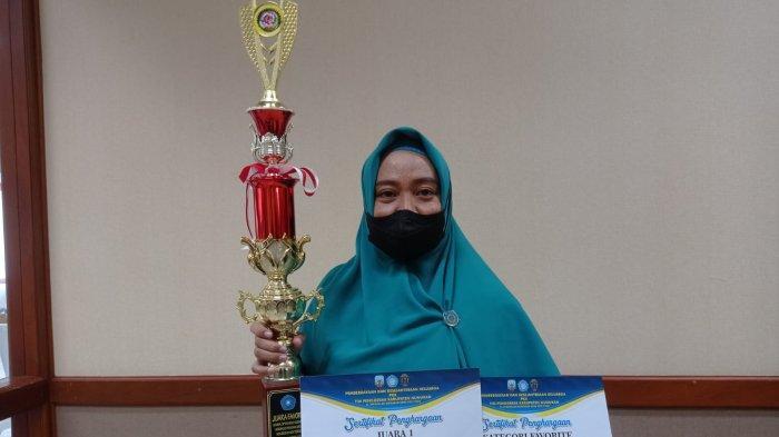 Astuti memegang piala dan sertifikat sebagai Juara I dan Kategori Favorit, Rabu (13/10/2021). TRIBUNKALTARA.COM/FEBRIANUS FELIS