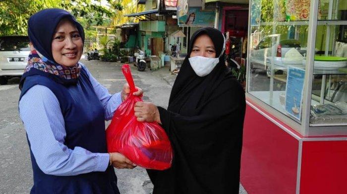 Ketua Alumni Smakar Balikpapan menyerahkan paket sembako kepada warga pada kegiatan baksos alumni.