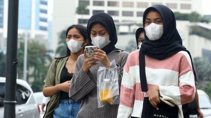 Warga beraktivitas menggunakan masker di kawasan Bundaran HI, Jakarta