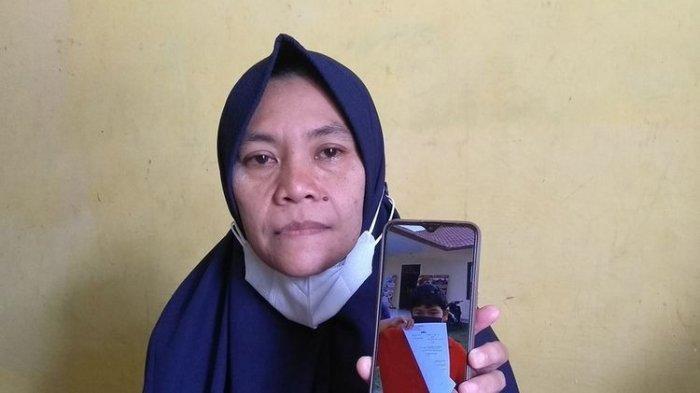 ANAK DIGIGIT ANJING - Lia Pratiwi (42) menunjukkan foto anaknya, M. Reza Aulia (10) membawa berkas laporan di Polsek Tuntungan pada Jumat (11/6/2021). Sebelum meninggal dunia pada Minggu (13/6/2021), Reza digigit anjing pada Kamis (10/6/2021). Kondisinya dari hari ke hari semakin memburuk. Pihak keluarga membuat laporan ke polisi lantaran tidak ada itikad baik dari pemilik anjing.