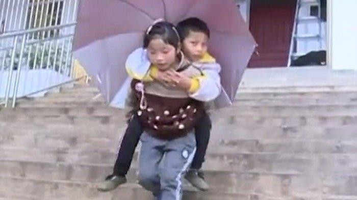 Salut, Bocah Perempuan Ini Rela Gendong Kakaknya yang Lumpuh ke Sekolah Setiap Hari