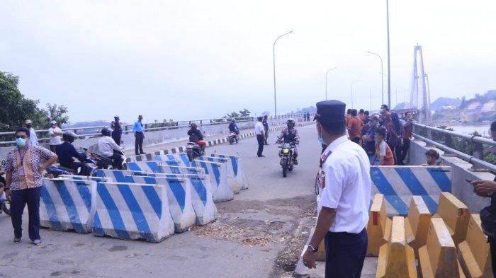 PEMBUKAAN JEMBATAN MAHKOTA II - Polisi lalu lintas dan petugas Dishub memgatur lalu lintas ketika pengendara bermotor melintasi jalur jalan Jembatan Mahkota II kini bernama Jembatan Ahmad Amins menuju Jalan Kapten Soedjono Sambutan Kota Samarinda Kalimantan Timur, Kamis (10/6/2021). Jembatan Mahkota II kembali dibuka setelah lebih dari 1 bulan ditutup pasca abrasi tanah di bawah pilon jembatan sisi Kecamatan Palaran.TRIBUNKALTIM.CO, NEVRIANTO HARDI PRASETYO