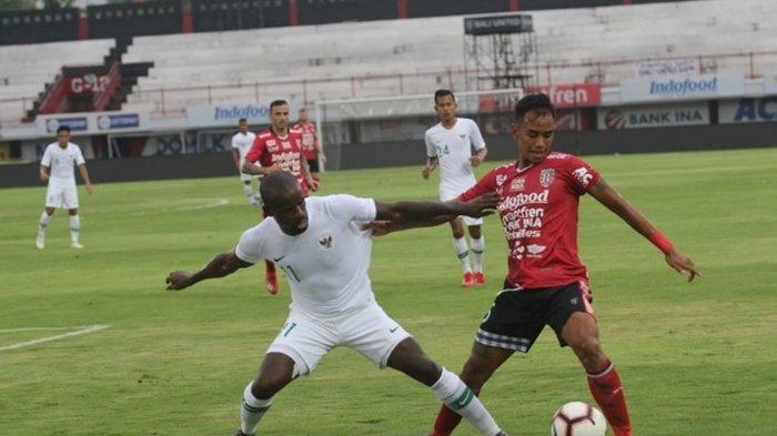 Pemain Timnas Indonesia Greg Nwokolo berebut bola dengan pemain Bali United dalam laga uji coba Rabu (20/3/2019)