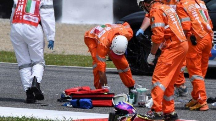 Petugas medis membersihkan lintasan saat mereka mengevakuasi pebalap Moto3 Jason Dupasquier dengan helikopter yang mengalami kecelakaan saat sesi kualifikasi MotoGP Italia di Mugello di pada 29 Mei 2021.