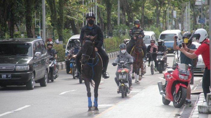 Rahmad Mas'ud menunggangi kuda hitam di lapangan Merdeka sambil mengajak anak-anak naik kuda