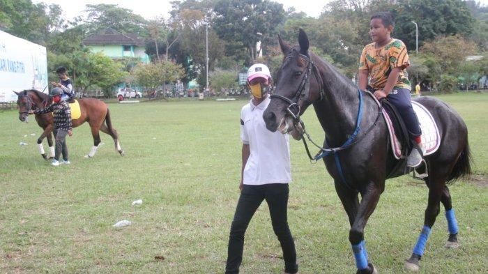 Salah seorang anak sedang menaiki kuda milik Rahmad Masud saat di Lapangan Merdeka Balikpapan