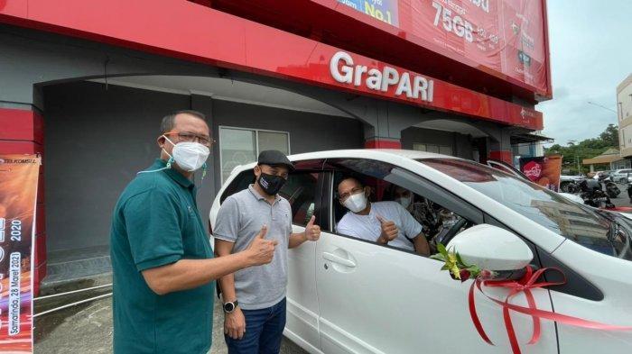 Irfan, Pemilik R JR 2 Cell, mitra outlet di Kota Samarinda  menerima hadiah mobil Toyota Avanza dari manajemen Telkomsel.