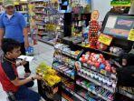 karyawan-memeriksa-barang-dagangan-yang-dipajang-di-etalase-minimarket-alfamart.jpg