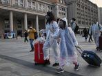 orang-orang-mengenakan-pakaian-pelindung-tiba-di-stasiun-kereta-api-fix.jpg