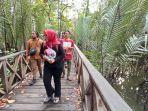 pengunjung-berjalan-menyusuri-hutan-mangrove-sambil-menikmati-pesona-wisata-alam.jpg