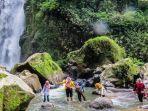 pengunjung-menyeberangi-sungai-menuju-air-terjun-kedung-kayang.jpg