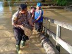 petugas-gabungan-dan-warga-saat-melakukan-pembersihan-di-sekitar-lokasi-banjir.jpg