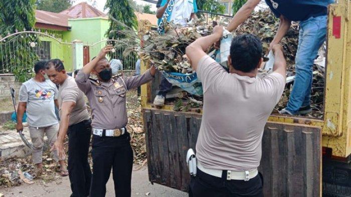 Anggota Ditlantas Polda NTT saat membantu membersihkan sampah pada salah satu titik di Kota Kupang, Senin 12 April 2021.