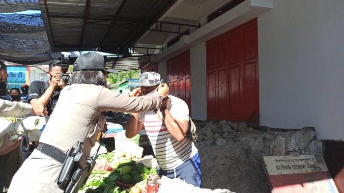 Kapolsek Oebobo AKP Magdalena Golu mere saat memakaikan masker pada pedagang di Pasar Kasih Naikoten 1 Kupang, Kamis (10/9)