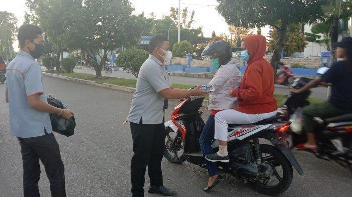 Karyawan PT Pos Atambua saat membagi takjil kepada pelintas jalan di Kota Atambua, Rabu 14 April 2021.