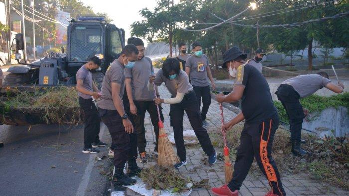 Personil dari Polda NTT sedang membersiahkan sampah, Jumat (23/4)