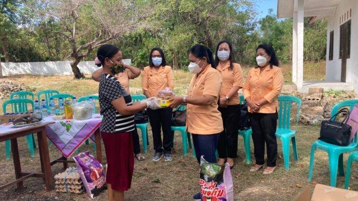 Ketua DWP UP Dinas Pendidikan NTT, Ny.Angela Deran menyerahkan bantuan berupa gula merah