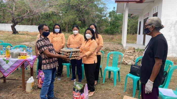 Sekretaris Dharma Wanita Persatuan Provinsi NTT, Ny.Rara H Lola menyerahkan bantuan kepada Pejabat  Kepala Desa Nunkurus, Marthen Bates, SST, Kamis 10 Juni 2021