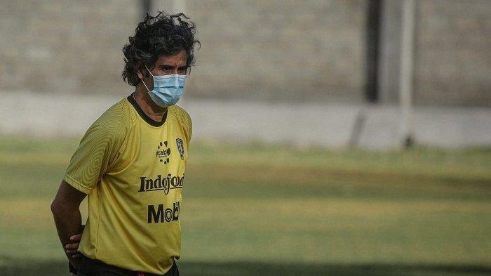 Pelatih Bali United Teco mengenakan masker saat memimpin latihan skuatnya.