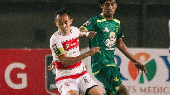 Ady Setiawan (kanan) berduel dengan kapten Madura United.