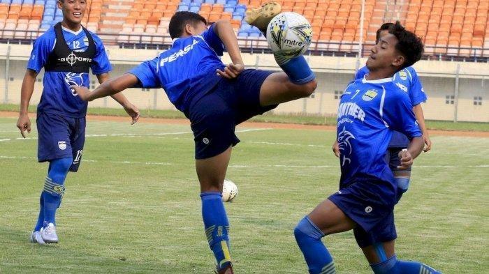 BEREBUT BOLA: Pemain Persib Bandung Beckham Putra Nugraha (kanan) berebut bola dengan Erwin Ramdani saat mengikuti latihan di Stadion Si Jalak Harupat, Kabupaten Bandung, Kamis (19/12).