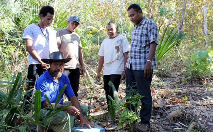 Yohanes Asafa (berdiri kanan) bersama masyarakat Kolhua, Kamis (22/8/2013), menunjuk patok batas yang berada di lahan masyarakat yang bakal menjadi lokasi pembangunan Bendungan Kolhua.