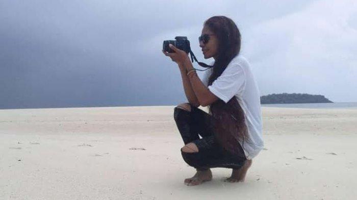 Salah satu wisatawan lokal saat berpose di lokasi wisata pasir timbul Meko