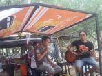 deni-haba-bermain-gitar-dengan-latar-belakang-mobil-deha-cafe-a.jpg