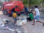 masyarakat-sedang-menampung-air-bersih-yang-didistribusikan-mobil-tangki-bpbd-kabupaten-tts_20181002_191433.jpg