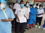 para-perawat-yang-sedang-berdiri-dengan-memegang-sehelai-kertas-putih.jpg
