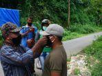 philipus-kami-ketua-aman-saat-membagikan-masker-kepada-warga-di-desa-nua-ja.jpg