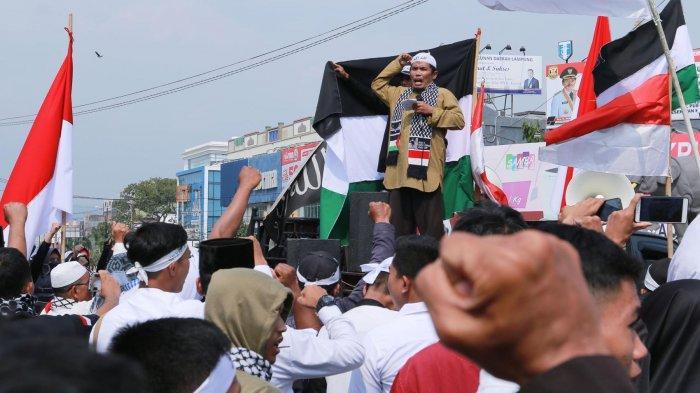 Ratusan Jamaah Muslimin (Hizbullah) dan Pondok Pesantren Alfatah Natar serentak mengucap takbir dan lakukan aksi kecaman dan kutukan terhadap Zionis Israel serta sekutunya, di Bundaran Tugu Adipura, Rabu (14/8/2019).