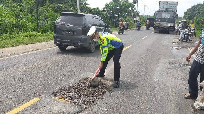 Antisipasi Lakalantas, Petugas Satlantas Polres Timbun Jalan Berlubang dengan Batu