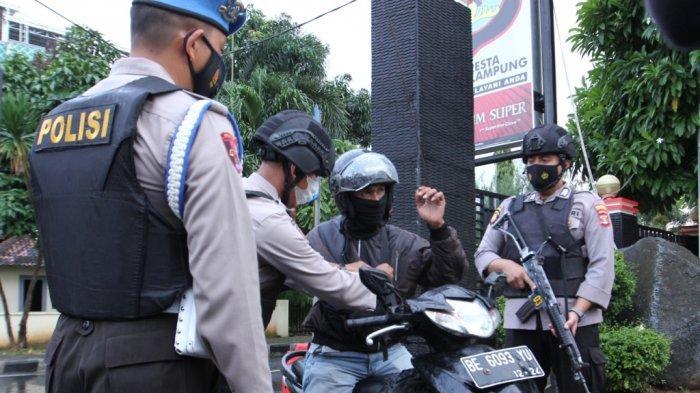 Sejumlah personel bersenjata lengkap ditugaskan untuk memeriksa tamu yang datang ke Mapolresta Bandar Lampung, Rabu (31/3/2021).